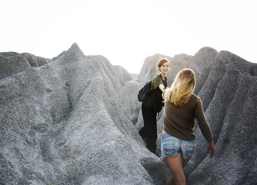Femme tenant main autre femme falaise