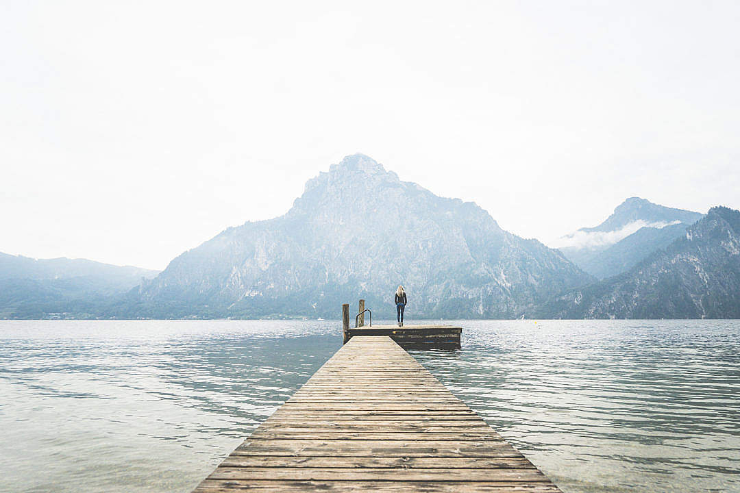Woman standing alone on a large wooden pier on a lake free stock photos picjumbo dsc00787 1080x720